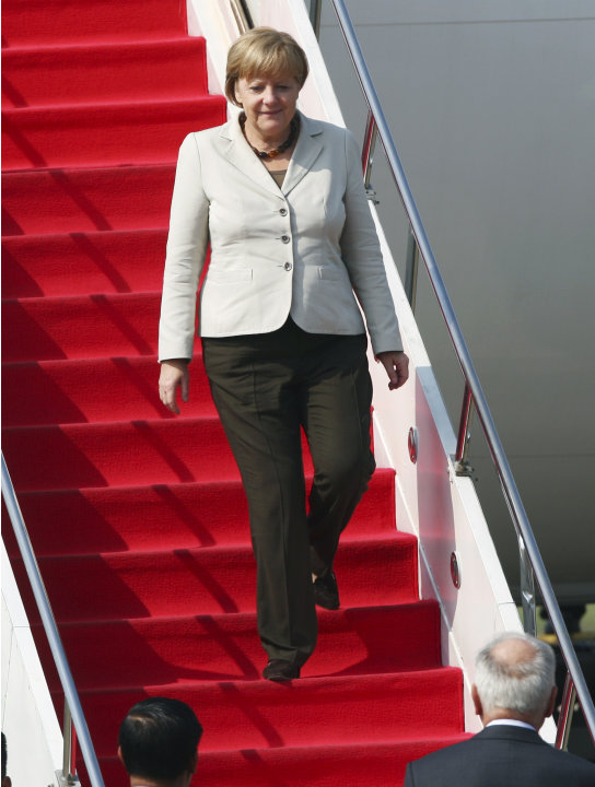 German Chancellor Angela Merkel steps down the stairs of her plane upon arrival at Halim Perdanakusuma airport in Jakarta, Indonesia, Tuesday, July 10, 2012. (AP Photo/Tatan Syuflana)