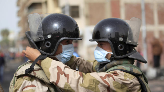 An Egyptian army soldier helps another soldier with a mask as troops take control of the state security building after several days of clashes between protesters and riot police in Port Said, Egypt, Friday, March 8, 2013. With the country in chaos from weeks of protests against the Islamist president, the police have now joined the fray, launching their own protests. Some security forces in Port Said have refused to leave their barracks to move against protesters in the street amid clashes raging for days. Others have refused orders to deploy to Port Said from elsewhere to help in the fight. (AP Photo/Khalil Hamra)