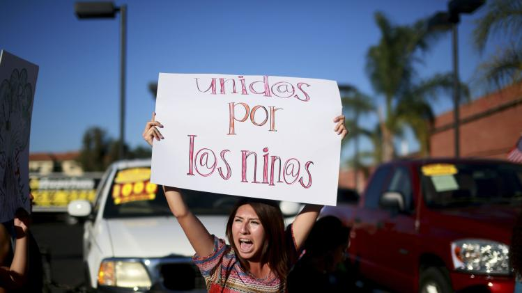 Pro-Immigration protester Gonzales holds up a poster while demonstrating outside the Escondido City Hall, north of San Diego