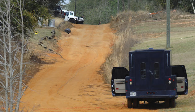 Police vehicles are staged near where a gunman has positioned himself below ground with a child hostage, in Midland City, Ala. on Wednesday Jan. 30, 2013. Authorities were locked in a standoff Wednesd