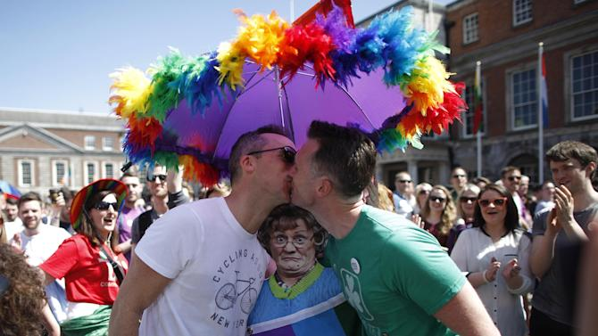 """Two men kiss as first results start to filter through in the referendum, Dublin, Ireland, Saturday, May 23, 2015. Ireland has voted resoundingly to legalize gay marriage in the world's first national vote on the issue, leaders on both sides of the Irish referendum declared Saturday even as official ballot counting continued. Senior figures from the """"no"""" campaign, who sought to prevent Ireland's constitution from being amended to permit same-sex marriages, say the only question is how large the """"yes"""" side's margin of victory will be from Friday's vote. (AP Photo/Peter Morrison)"""
