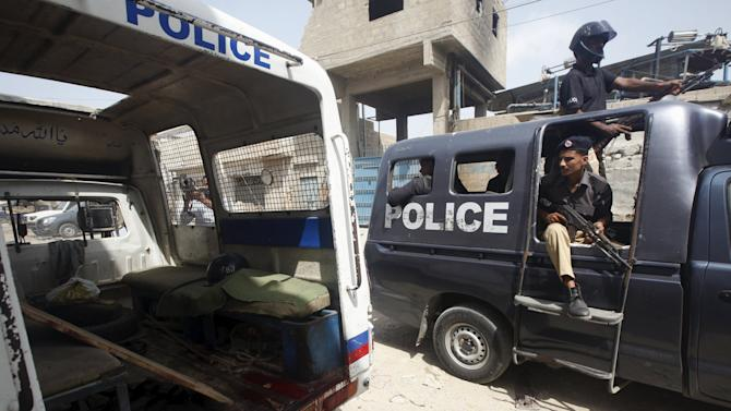 A police van passes a damaged police vehicle with blood stains, after three policemen were killed by unidentified gunmen, in Karachi