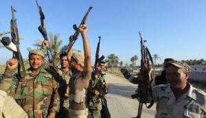 Shi'ite fighters and Iraqi army members celebrate…