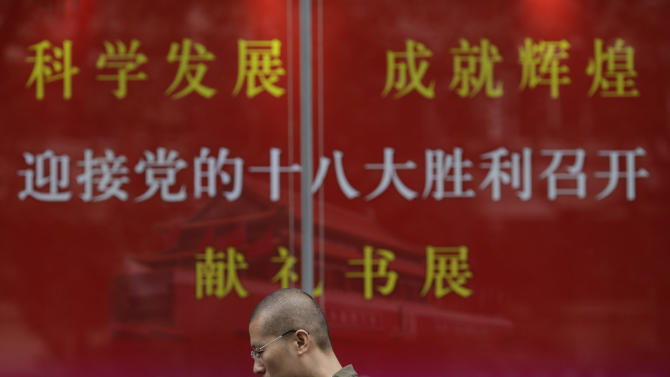 A man walks past an official propaganda to welcome the Chinese Communist Party's 18th Congress which held in Beijing, at a bookstore in Shanghai, China, Thursday Nov. 8, 2012. China's ruling Communist Party opened a congress Thursday to usher in a new group of younger leaders faced with the challenging tasks of righting a flagging economy and meeting public calls for better government. (AP Photo/Eugene Hoshiko)