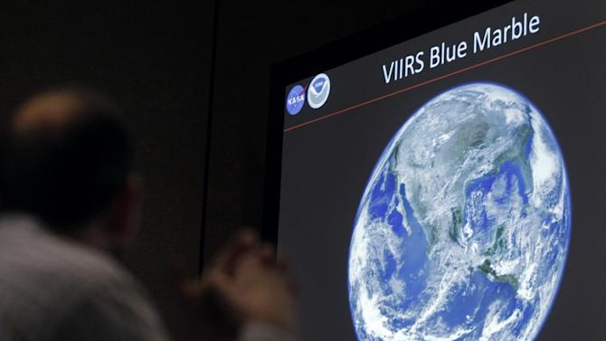 A man looks at a view of Earth from space during a media conference Wednesday, Dec. 5, 2012, at the American Geophysical Union meeting in San Francisco. The National Aeronautics and Space Administration has released new composite images of earth taken by the National Oceanic and Atmospheric Administration's Suomi National Polar-orbiting Partnership satellite. A new sensor aboard the NPP satellite is enabling scientists to observe Earth's atmosphere and surface during nighttime hours, in greater detail than ever before. (AP Photo/Ben Margot)
