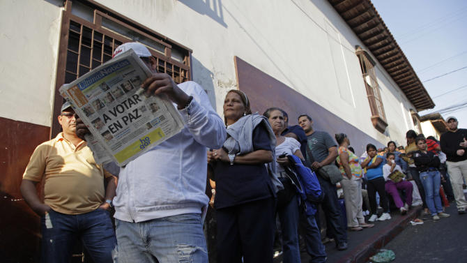 "Residents wait in line to enter a polling station during the presidential election in Caracas, Venezuela, early Sunday, April 14, 2013. Interim President Nicolas Maduro, who served as the late President Hugo Chavez's foreign minister and vice president, is running against opposition candidate Henrique Capriles. The newspaper's headline reads in Spanish ""Vote in Peace."" (AP Photo/Ariana Cubillos)"