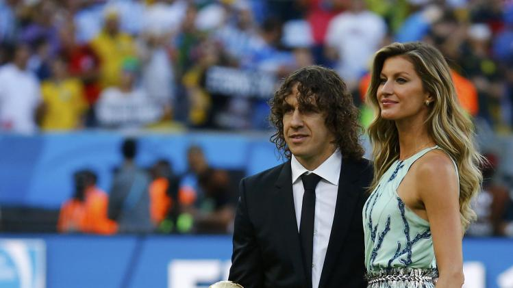 Puyol and Brazilian supermodel Bundchen pose with the World Cup trophy before the 2014 World Cup final in Rio de Janeiro