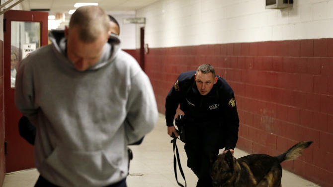 Jersey City Police Department officer Eric Petersen, center, holds on to his police dog, Ali, as Camden Police Officer Allen Williams, obstructed, apprehends JCPD officer Michael O'Connell, left, during a training exercise at the New Jersey Department of Public Works, Tuesday, Jan. 29, 2013, in Jersey City, N.J. Officers from various agencies are participating in the police dog class, which graduates on Feb. 8. (AP Photo/Julio Cortez)
