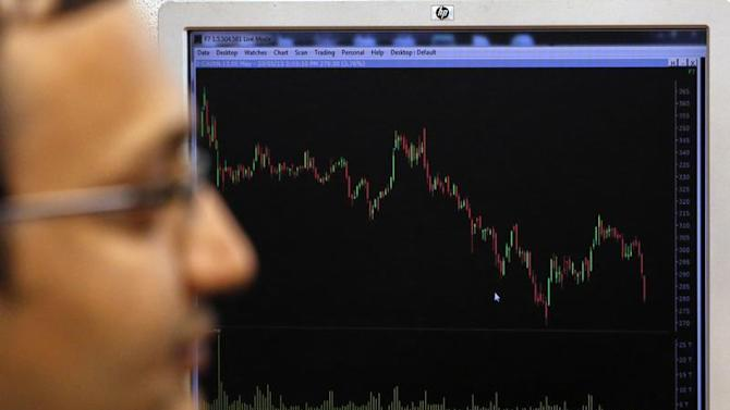 A broker works while sitting in front of a screen displaying live stock quotes on the floor of a trading firm in Mumbai