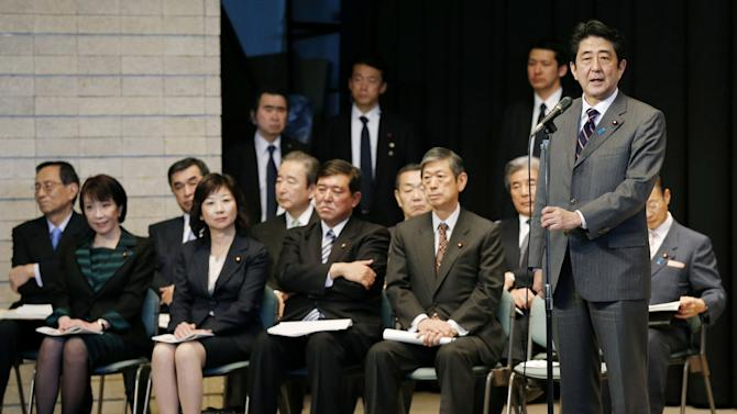 Japan's prime-minister-to-be Shinzo Abe, right, along with his top lieutenants, delivers a speech in front of his Liberal Democratic Party lawmakers ahead of the special diet session, at the party headquarters in Tokyo, Wednesday, Dec. 26, 2012. Capitalizing on the Democrats' failure to improve the economy and its perceived lack of strong leadership, Abe led the Liberal Democratic Party to victory in parliamentary elections Dec. 16. Abe was to be named prime minister later Wednesday. He was also prime minister in 2006-2007.  (AP Photo/Kyodo News) JAPAN OUT, MANDATORY CREDIT, NO LICENSING IN CHINA, HONG KONG, JAPAN, SOUTH KOREA AND FRANCE
