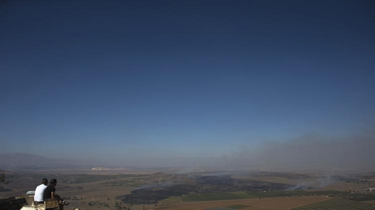 Israelis look at smoke rising on the Israeli-controlled side of the line dividing the Israeli-occupied Golan Heights from Syria following fighting near the Quneitra border crossing