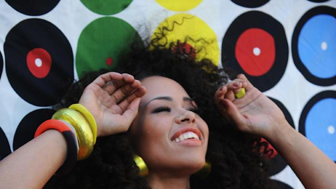 """This Sept. 18, 2011 publicity photo provided by RCA Records/PictureGroup shows the making of the Sony Music video with Elle Varner featuring J.Cole in the Williamsburg section of New York. When Varner made her debut to the music world with her first music video, she did so in a hand-me-down. """"The jacket I'm wearing in the """"Only Wanna Give It to You"""" (music video) was $4 at Good Will,"""" she said of the bright orange blazer that got attention on urban blogs when the video was released in 2011. (AP Photo/ RCA Records/PictureGroup, Brad Barket)"""