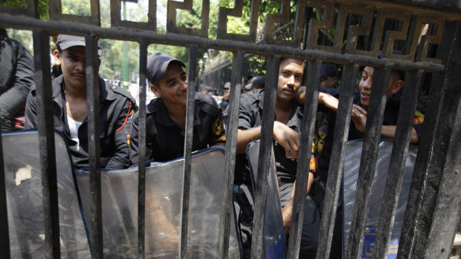 Anti-riot soldiers sit behind a closed gate barring entry to the Egyptian Parliament in Cairo, Egypt, Tuesday, June 19, 2012.   Egypt's highest court has ordered the country's Islamist-dominated parliament dissolved, saying its election about six months ago was unconstitutional. (AP Photo/Amr Nabil)