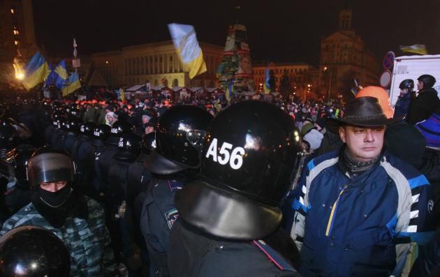 Pro-European integration protesters line up in front of riot police at Independence Square in Kiev