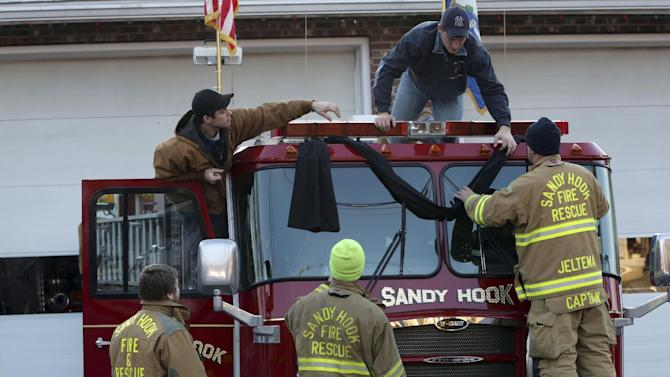 Sandy Hook firefighters hang bunting on their firetruck, Saturday, Dec. 15, 2012 in Sandy Hook village of Newtown, Conn.   The massacre of 26 children and adults at Sandy Hook Elementary school elicited horror and soul-searching around the world even as it raised more basic questions about why the gunman, 20-year-old Adam Lanza, would have been driven to such a crime and how he chose his victims.  (AP Photo/Mary Altaffer)