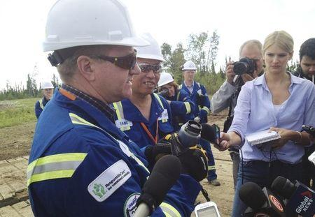 Senior Vice President Canadians operations Ron Bailey and CEO Fang Zhi show a jar of bitumen at Nexen spill site near Nexen Energy's Long Lake oilsands facility south of Fort McMurray