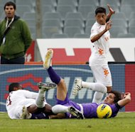 Fiorentina's Stevan Jovetic, of Montenegro, right, is fouled by AS Roma's Juan, of Brazil, during a Serie A soccer match at the Artemio Franchi stadium in Florence, Italy Sunday, Dec. 4, 2011. (AP Photo/Fabrizio Giovannozzi)