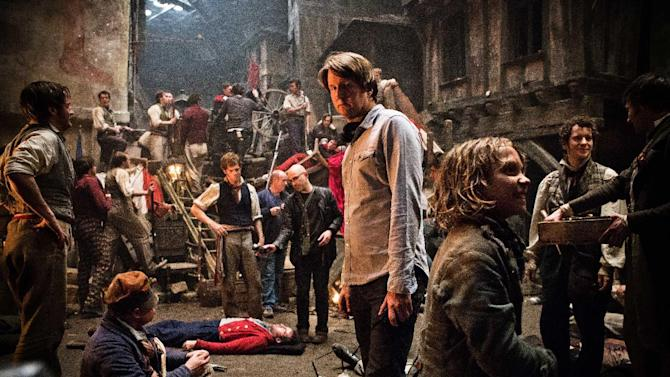 "This undated publicity photo provided by Universal Pictures shows Oscar®-winning director, Tom Hooper, center, and Daniel Huttlestone, right, as Gavroche on the set of Hooper's new film, ""Les Misérables,"" the motion-picture adaptation of the beloved global stage musical adapted from Victor Hugo's novel. (AP Photo/Universal Pictures/James Fisher)"