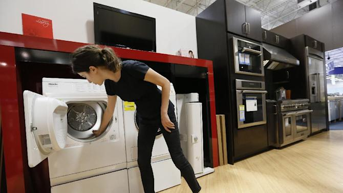 In this photo taken Friday, Apr. 26, 2013, Miele Account Manager Natasha Feldman showcases Miele washer and dryer energy efficient appliances at the Pacific Sales at the Best Buy store in Glendale, Calif. The Commerce Department reports on business orders for durable goods in April on Friday, May 24, 2013. (AP Photo/Damian Dovarganes)
