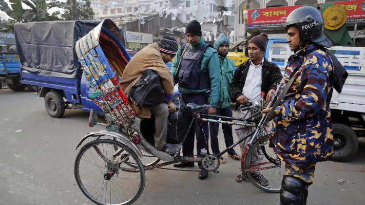 Bangladeshi policemen check passengers riding on a rickshaw during a nationwide 48-hour strike called by the main opposition Bangladesh Nationalist Party (BNP) a day before general elections in Dhaka, Bangladesh, Saturday, Jan. 4, 2014. The run-up to Sunday's general election in Bangladesh has been marked by bloody street clashes and caustic political vendettas, and the vote threatens to plunge this South Asian country even deeper into crisis. (AP Photo/Rajesh Kumar Singh)
