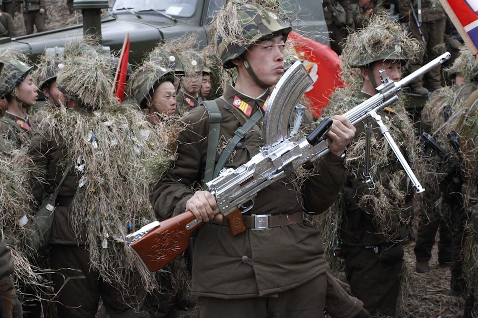 In this Sunday March 4, 2012 photo, North Korean soldiers, including one carrying a weapon that military personnel say was given to them by North Korean leader Kim Jong Un,  gather at a military base on North Korea's southwest coast, opposite South Korea's Baengnyeong Island. (AP Photo/Kim Kwang Hyon)
