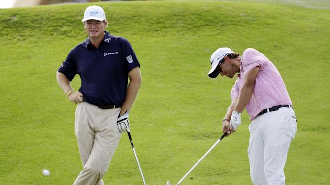 Adam Scott, of Australia, hits from the 14th tee as Ernie Els, left, of South Africa, watches during a practice round for the PGA Championship golf tournament on the Ocean Course of the Kiawah Island Golf Resort in Kiawah Island, S.C., Wednesday, Aug. 8, 2012. (AP Photo/Chuck Burton)