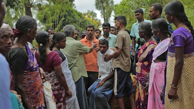 Sri Lankans try to console a man, sitting center, whose relatives are missing at the site of a mudslide at the Koslanda tea plantation in Badulla district, about 220 kilometers (140 miles) east of Colombo, Thursday, Oct. 30, 2014. Disaster Management Minister Mahinda Amaraweera estimated the number of dead in Wednesday's disaster would be fewer than 100, although villagers said the figure could easily exceed 200. (AP Photo/Eranga Jayawardena)
