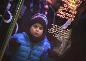 "A boy looks in the window as he lines up outside a Toys""R""Us store in Times Square before their Black Friday Sale in New York"