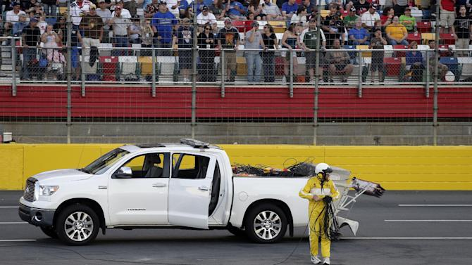 A worker cleans up a broken television camera cable that damaged several race cars during the NASCAR Sprint Cup series Coca-Cola 600 auto race at Charlotte Motor Speedway in Concord, N.C., Sunday, May 26, 2013. (AP Photo/Nell Redmond)