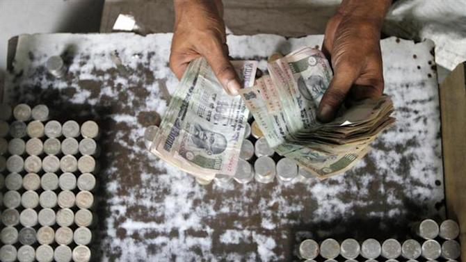 A man exchanging damaged Indian currency counts 100 rupee notes along a roadside in Kolkata August 30, 2013.
