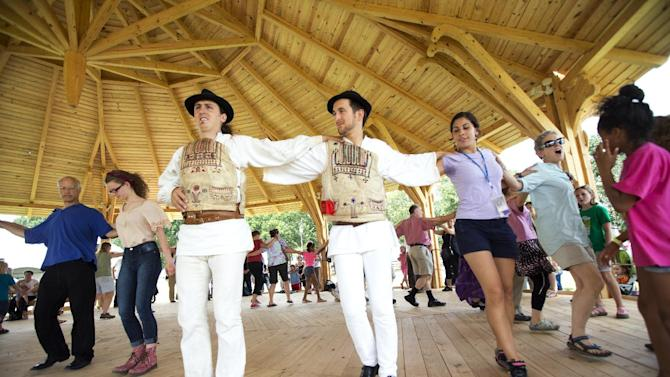 """In this July 3, 2013 photo, Hungarians, from left, Andre Csaba and Lorand Bodor, lead festival visitors in dancing the Hejsza, a Hungarian folk dance, in the Dance Barn, at the 47th annual Smithsonian Folklife Festival on the National Mall in Washington. Hungarian structures are part of the """"Hungarian Roots to Revival"""" program in this year's Smithsonian Folklife Festival _ and a personal thrill for the team of carpenters from Hungary who arrived a month prior to the festival to construct the 23-foot Peacock Tower, the Dance Barn and other buildings. (AP Photo/Manuel Balce Ceneta)"""