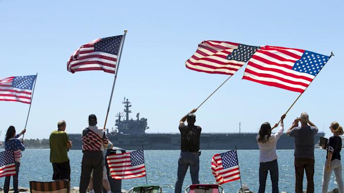 Supporters wave American flags along shoreline as USS Ronald Reagan departs for Yokosuka, Japan from Naval Station North Island in San Diego