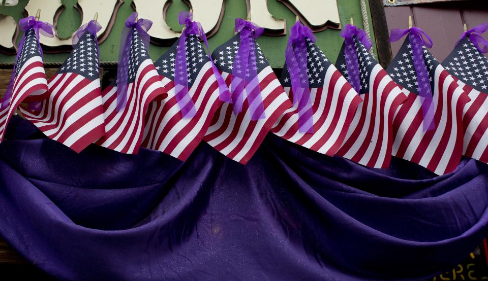 United States flags draped with purple bunting and ribbons hang above Matt's Saloon, along Whiskey Row, Friday, July 5, 2013 in Prescott, Ariz. The flags and ribbons were hung in honor of the 19 fallen Granite Mountain Hotshot firefighters who died battling a blaze near Yarnell, Ariz. on Sunday. (AP Photo/Julie Jacobson)