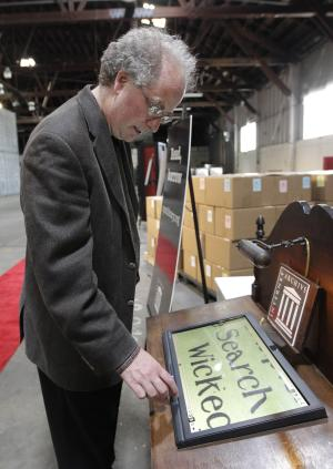"In this July 21, 2011 photo, Brewster Kahle, digital librarian for the Internet Archive, demonstrates the zoom function while scanning a book on a touch screen at the Internet Archive's Physical Archive warehouse in Richmond, Calif.  Saving a copy of every Web page ever posted sounds like an ambitious life's work, but Khale has decided digital isn't enough. The founder of the Internet Archive wants to expand his effort to provide ""universal access to all knowledge"" by preserving a physical copy of every book ever written. (AP Photo/Jeff Chiu)"