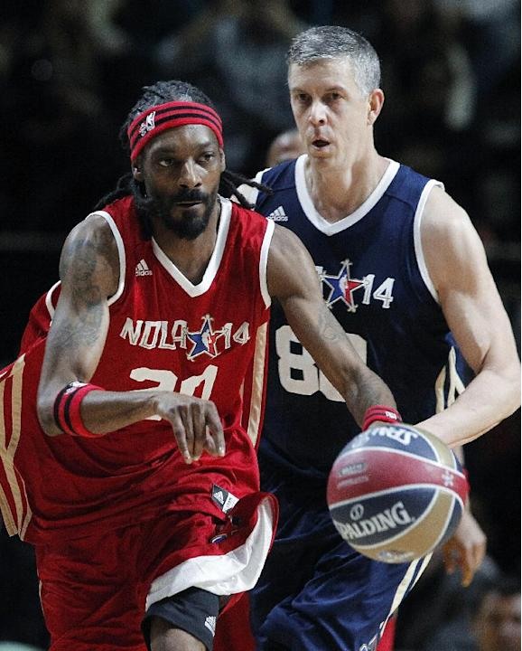 U.S. Education Secretary Arne Duncan, of the East team, follows West's Snoop Dogg, aka Snoop Lion, during the second half of the NBA All-Star Celebrity basketball game in New Orleans, Friday, Feb.