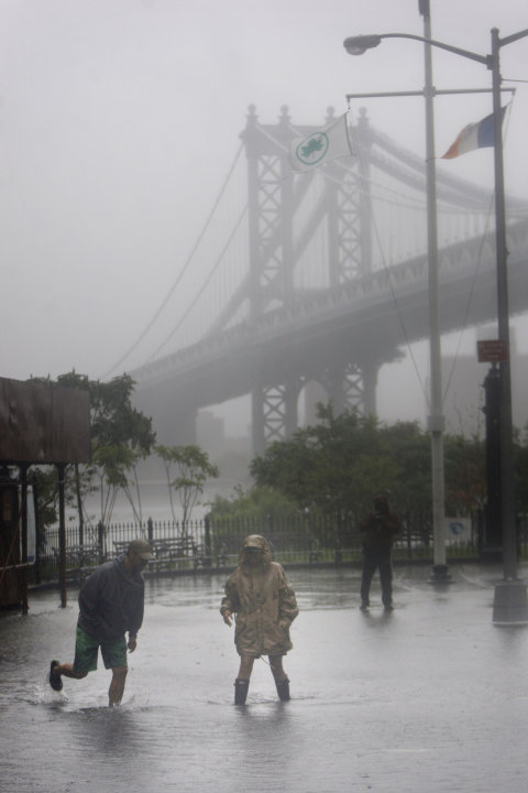 FILE - In this Aug. 28, 2011, file photo, people near New York's Brooklyn Bridge wade through floodwaters brought on by Hurricane Irene, which weakened to a tropical storm just before hitting New York