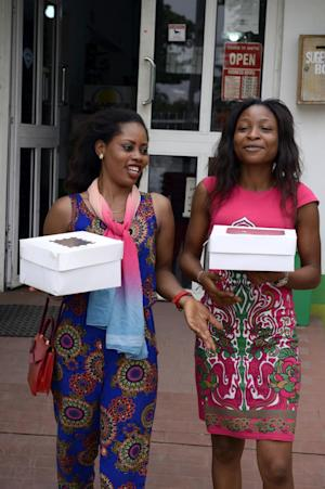 Two women walk holding Valentine cakes bought at a …