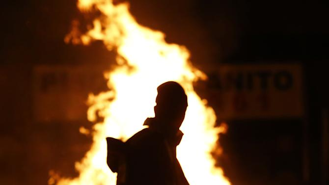 A protester walks past a burning barricade as he leaves the area after a demonstration near the stadium where Mexico and Japan played in a Confederations Cup soccer game in Belo Horizonte, Brazil, Saturday, June 22, 2013. Demonstrators once again took to the streets of Brazil on Saturday, continuing a wave of protests that have shaken the nation and pushed the government to promise a crackdown on corruption and greater spending on social services. (AP Photo/Bruno Magalhaes)