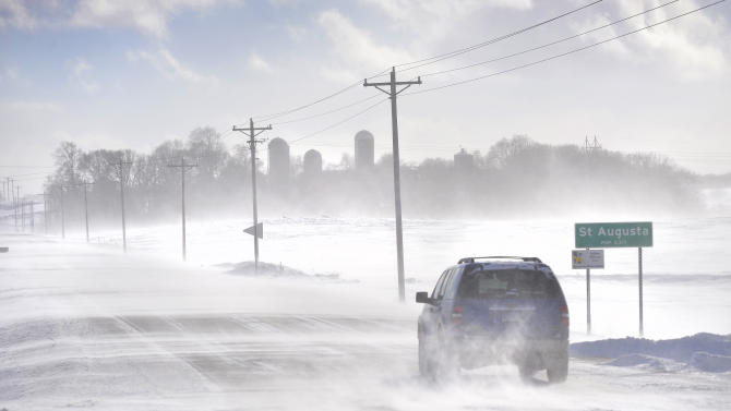 An SUV ventures past the St. Augusta, Minn., city limits sign on Stearns County Road 136 in near white-out conditions Sunday afternoon, Jan. 26, 2014 south of St. Cloud, Minn. An unusual weather pattern driving bitterly cold air from the Arctic Circle south across a huge swath of the Midwest is expected to send temperatures plummeting Monday from Minneapolis to Louisville, Ky., the latest punch from a winter that is in some areas shaping up as one of the coldest on record. (AP Photo/St. Cloud Times, Kimm Anderson) MANDATORY CREDIT