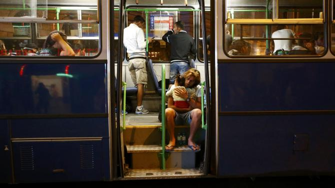 A man holds his child as he sits in a bus, which is supposed to leave to Austria and Germany, at the Keleti trainstation in Budapest