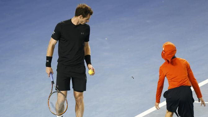 A ball boy runs across court as Andy Murray of Britain looks at an insect flying past, before he serves against Nick Kyrgios of Australia during their men's singles quarter-final match at the Australian Open 2015 tennis tournament in Melbourne