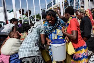 A woman carries a bucket as people queue for water …