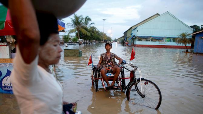 File photo shows a man sitting on his cart which he attached with National League for Democracy party flags along a flooded street in Yangon