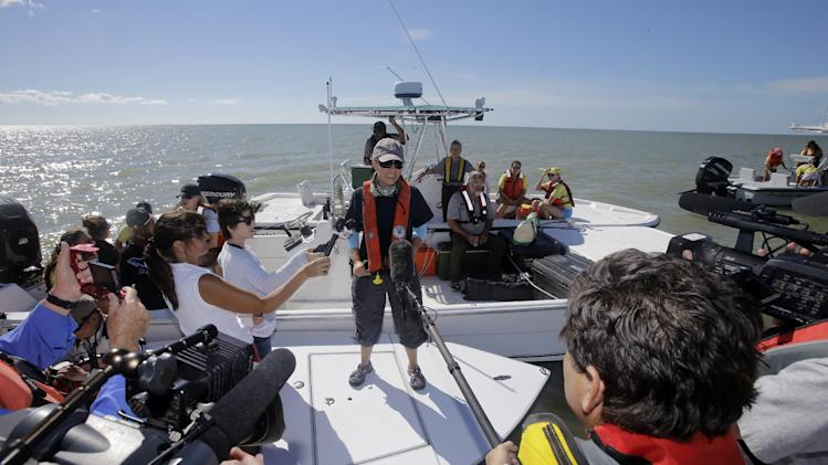 NOAA strandings official, Liz Stratton, informs reporters the pod in deeper water could reach as many as 30 animals and that they were about 11 miles offshore at midday,Thursday, Dec. 5, 2013, in the Everglades National Park, Fla. (AP Photo/Alan Diaz, Pool)