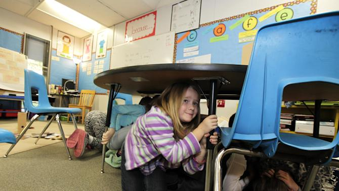 "Jaely John, 7, a student at Twin Lakes Elementary School in Federal Way, Wash.,  takes shelter under a table as she takes part in an earthquake drill, Thursday, Oct. 18, 2012. Millions of people took part in the ""Great Shakeout"" earthquake drill across the country and elsewhere Thursday to practice and prepare for the possibility of real quakes in the future. (AP Photo/Ted S. Warren)"