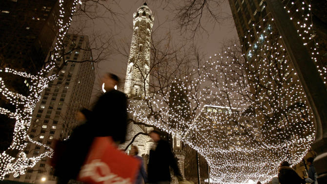 FILE - In this Nov. 25, 2005 file photo, shoppers walk under lights strung up for the holidays around Chicago's landmark Water Tower on Michigan Avenue in Chicago. A walk along The Magnificent Miles is a great, free way to take in Chicago's history, architecture and shopping. (AP Photo/Jeff Roberson, File)