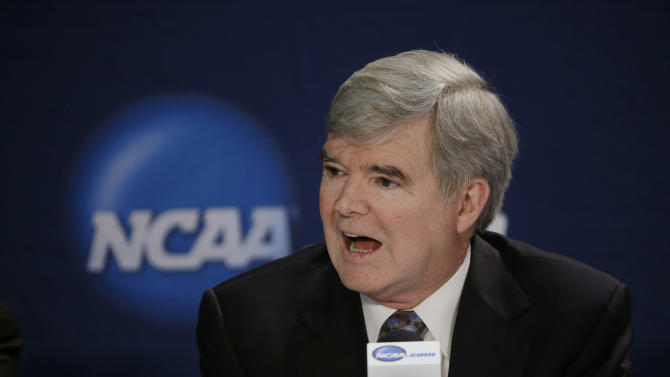 FILE - In this April 6, 2014, file phot, NCAA President Mark Emmert answers a question at a news conference in Arlington, Texas. Testifying in a landmark antitrust lawsuit filed against his organization, Emmert said Thursday, June 19, 2014, he believes there is a clear difference between the proposal to pay athletes a few thousand more dollars a year and giving them the equivalent of a salary. Emmert's testimony came in a much-anticipated appearance as the NCAA tries to convince U.S. District Judge Claudia Wilken that its system of so-called amateurism is not anti-competitive and is the best model for regulating college sports. (AP Photo/David J. Phillip, File)