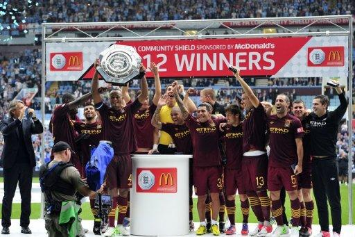Manchester City's Belgian defender Vincent Kompany lifts the trophy
