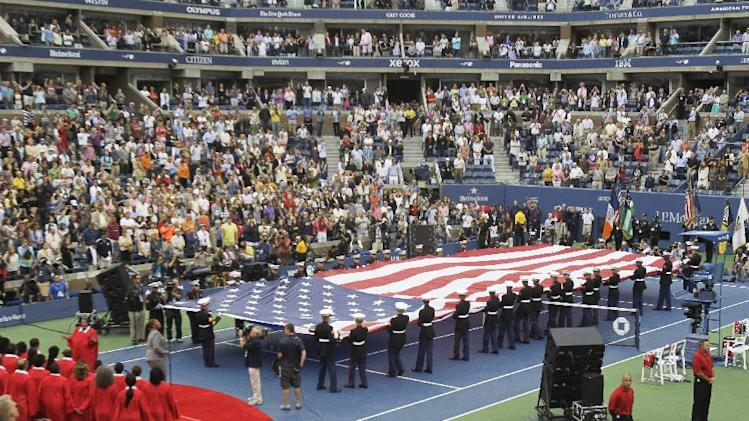Fans look on during the national anthem before the women's championship match between Serena Williams  and Samantha Stosur of Australia at the U.S. Open tennis tournament in New York, Sunday, Sept. 11, 2011. (AP Photo/Mike Groll)