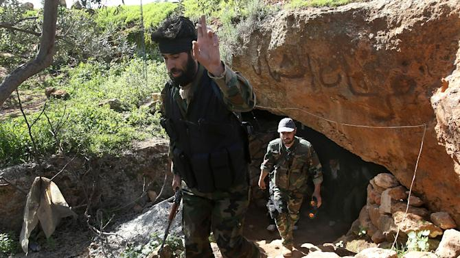 """A Free Syrian Army fighter, Abu al-Yaman, left, a commander of Knights of the North brigade, cheers as he leaves with other rebels one of their caves to reconnaissance a Syrian army forces base of al-Karmid, at Jabal al-Zaweya, in Idlib province, Syria, Wednesday, Feb. 27, 2013. Syrian warplanes carried out airstrikes on rebels trying to storm a police academy outside Aleppo on Wednesday, while jihadi fighters battled government troops along a key supply road leading to the southeastern part of the city, activists said. The Arabic words in the cave entrance read:""""Knights of the North brigade"""". (AP Photo/Hussein Malla)"""